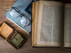 An older open book on top of a closed blue book, with glasses and a clock on a wooden table.